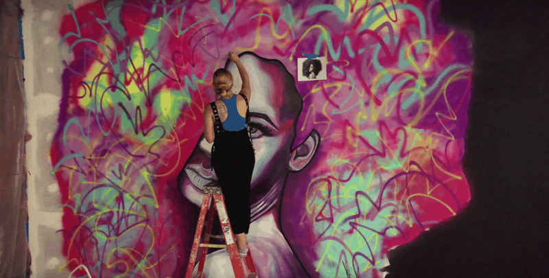 young artists collaborate, here devona stimpson is painting mural